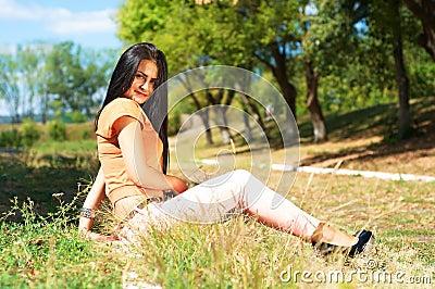 Porträt der jungen schönen lächelnden Frau draußen, genießend