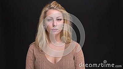 Porträt der kaukasischen langhaarigen Frau des Umkippens, die ruhig in Kamera auf schwarzem Hintergrund aufpasst stock video