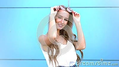 Porträt der lächelnden Frau der Schönheitsmode mit Fliegenfrisur, in der rosa Neonsonnenbrille auf blauem Hintergrund beil?ufig stock footage