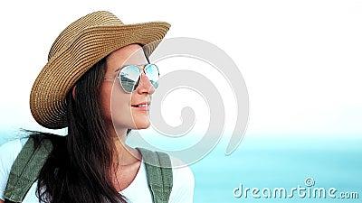 Porträt der nachdenklichen jungen Frau in der Sonnenbrille und im Hut mit Rucksack erstaunlichen Meerblick genießend stock video