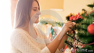 Porträt der schönen lächelnden Frau, die Weihnachtsbaum im Wohnzimmer mit buntem Flitter und Perlen verziert stock video