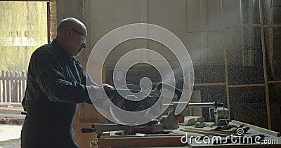 Porträt des männlichen kaukasischen Tischlers, der das Holz mit Kopfsäge in kleine Quadrate in der Fertigung schnitzt stock video