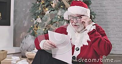 Porträt des Weihnachtsmanns, der Kaffee oder Tee trinkt und liest Alter Typ mit weißem Bart in Brille, der aussieht stock video footage