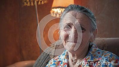 Porträt einer älteren Frau 80-90 Jahre alt zu Hause Alte sonderbare Dame mit dem geknitterten Hautgesicht, das Kamera betrachtet  stock video