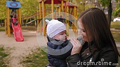 Porträt einer Mutter mit einem kleinen Sohn in einem Park im Frühling auf einem Spielplatz stock video