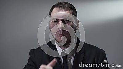 Porträt eines überzeugten bärtigen Mannes in einem Anzug, der die Kamera betrachtet Geschäftsmann, der Trauben isst stock footage