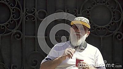 Porträt eines alten bärtigen modern zurechtgemachten trinkenden Kaffees und seinen grauen Bart draußen verdrehen des Großvaters stock video