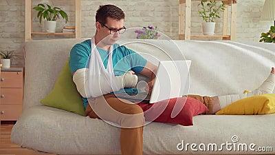 Porträt eines jungen Mannes mit einem gebrochenen Arm und einem Bein, die auf der Couch und dem Gebrauch ein Laptop sitzen stock footage
