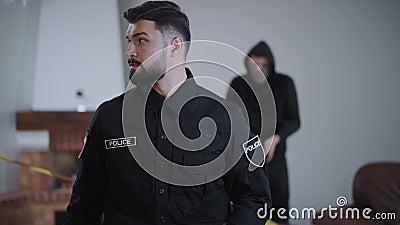 Porträt eines kaukasischen Polizeibeamten, der sich als kriminelles Umladen von Waffen im Hintergrund herumsieht Gefahr stock video