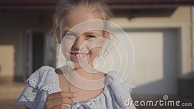 Porträt eines recht netten kleinen Mädchens, das einen Löwenzahn durchbrennt und das Kameralächeln betrachtet Die Kinderausgabenz stock footage