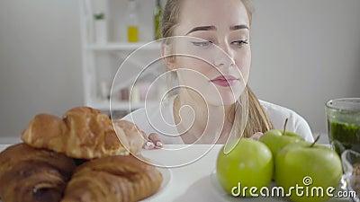 Porträt eines schönen schlanken Mädchens, das zwischen grünen Äpfeln und grausamen Croissants wählen kann Junge kaukasische Frau, stock video