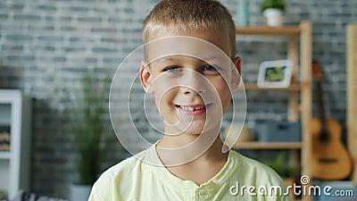 Portrait à mouvement lent de mignon petit garçon aux cheveux clairs regardant la caméra souriant banque de vidéos