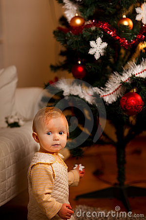 Portrait of adorable baby near Christmas tree