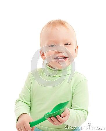 Portrait of adorable joyful boy with toy shovel