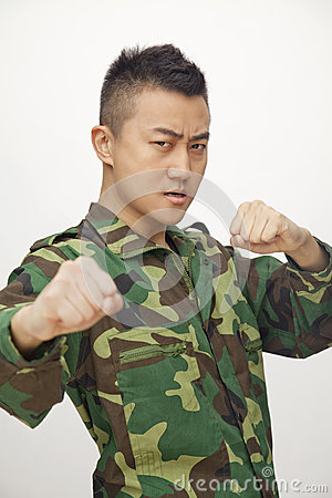 Portrait of aggressive young man in military uniform putting up fists to fight, studio shot