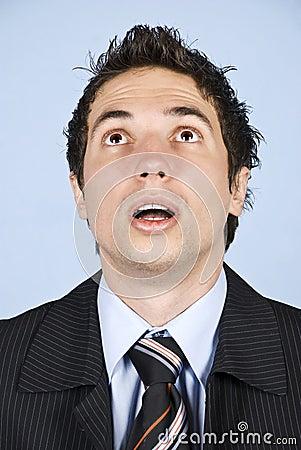 Portrait of amazed businessman looking up