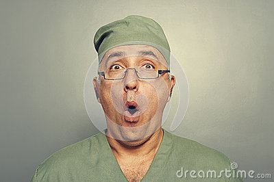 Portrait of amazed doctor over grey