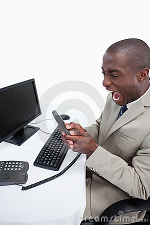 Portrait of an angry businessman answering the phone while using