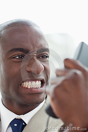 Portrait of an angry businessman looking at his phone handset