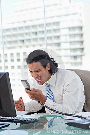 Portrait of a angry businessman shouting at his handset
