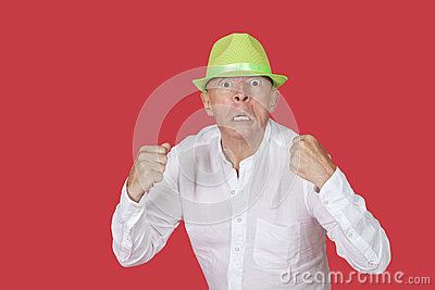 Portrait of an angry senior man clenching fists against red background