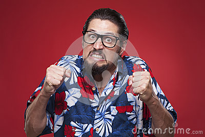 Portrait of a angry young man in Hawaiian shirt with clenched fi