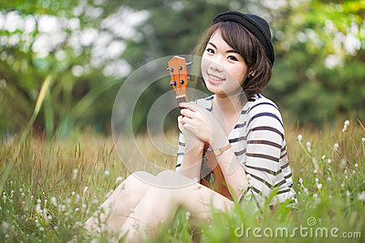 Portrait of Asia women playing Ukulele in meadow