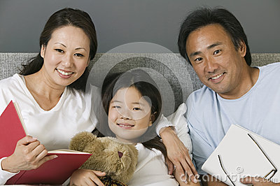 Portrait of an Asian family in bed at home