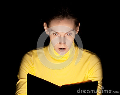 Young woman reading book surprised wondering