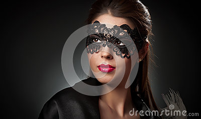 Portrait of attractive sensual young woman with mask. Young attractive brunette lady posing on dark background in studio. Portrait
