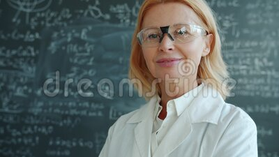 Portrait of attractive woman medical researcher in white gown and goggles indoors. Chalkboard with formulas is in background. People and profession concept stock video footage