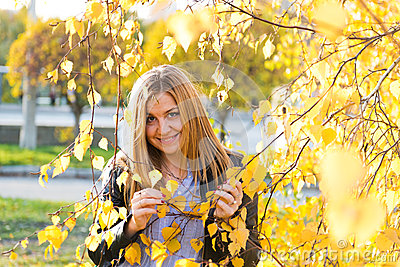 Portrait of autumn woman with yellow leaves