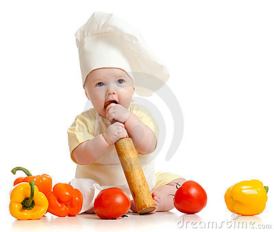 Portrait of a baby in chef hat with healthy  food