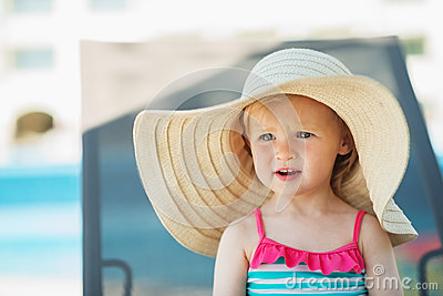 Portrait of baby in hat sitting on sunbed