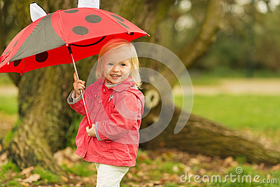 Portrait of baby with red umbrella outdoors