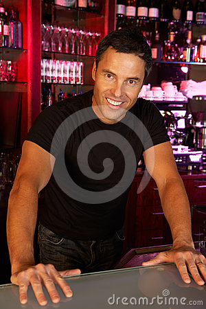 Portrait Of Barman Standing Behind Bar