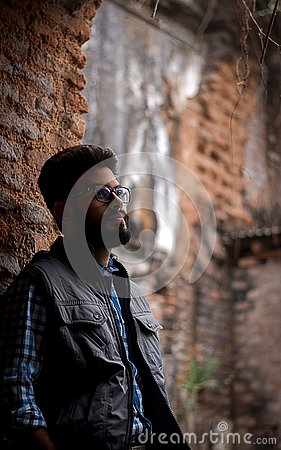 Fashion portrait of Bearded Guy on the front of old buildingTAKI RAJBARI Stock Photo