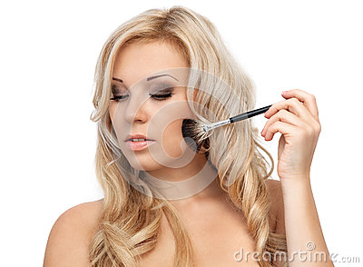 Portrait of a beautiful blonde girl with makeup brush