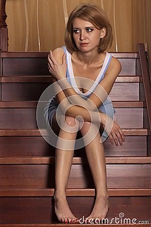 Portrait beautiful blonde sits on ladder