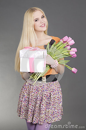 Portrait of beautiful blondie girl with gift and flowers
