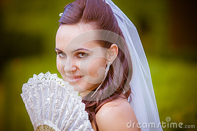 Portrait of the beautiful bride with a fan