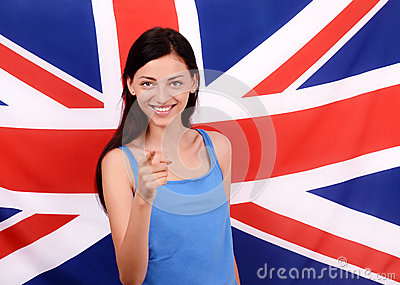 Portrait of a beautiful British girl smiling and pointing in front to you.