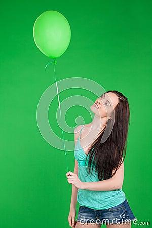 Portrait of beautiful brunette smiling girl wearing shorts holdi