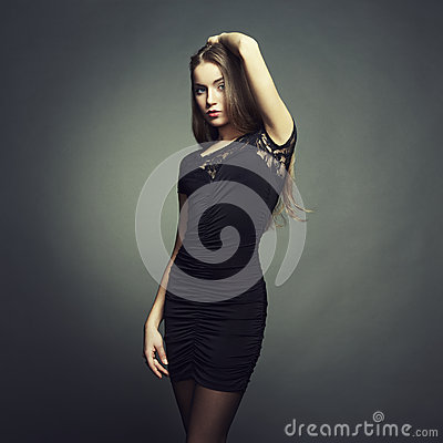 Portrait of beautiful brunette woman in black dress. Fashion pho