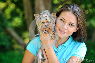 Portrait of a beautiful girl with her puppy in a park - closeup