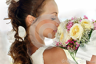 Portrait of a beautiful girl in white with a wedding bouquet.