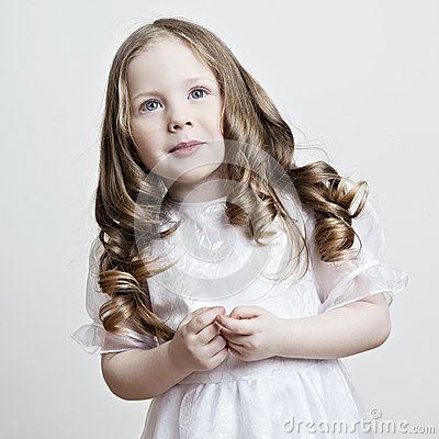 Portrait of a beautiful little girl in a white dress and veil on