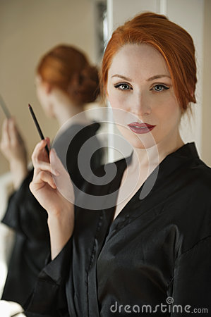 Portrait of a beautiful redheaded woman in robe holding a lip liner