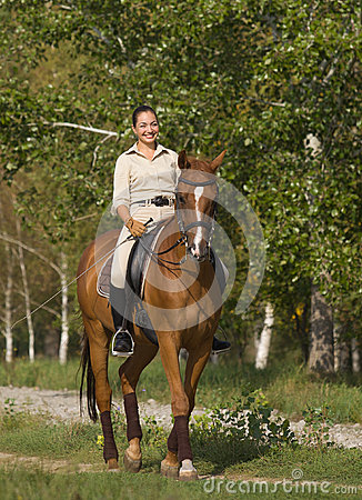 Portrait of beautiful smiling brunette horsewoman