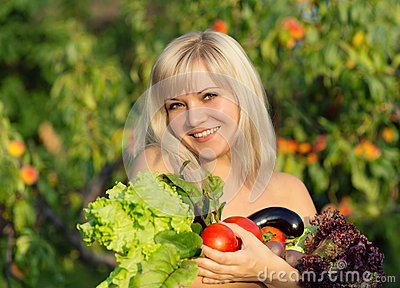 Portrait of beautiful smiling girl with vegetables and herbs